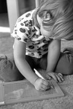 Anne, 4 ans, écrit sur son ardoise magique.